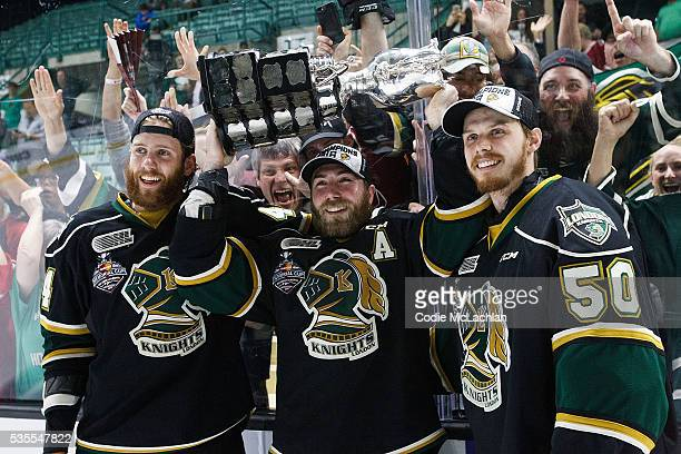 Jacob Graves Aaron Berisha and goaltender Brendan Burke of the London Knights hoist the Memorial Cup with fans after defeating the RouynNoranda...