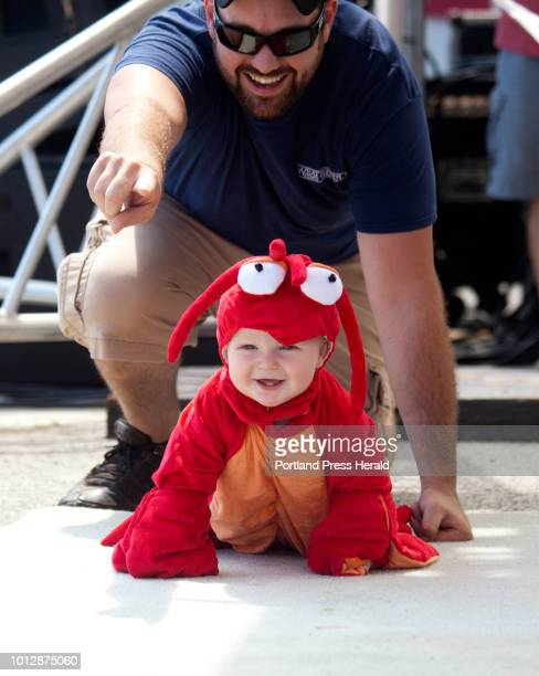 Jacob Harper of Owls Head encouraged his son Lincoln 11 months to crawl forward during the diaper derby at the Maine Lobster Festival in Rockland on...