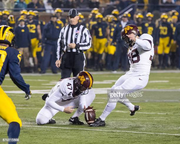 Jacob Herbers of the Minnesota Golden Gophers holds the football for kicker Emmit Carpenter on a point after attempt in the first quarter against the...