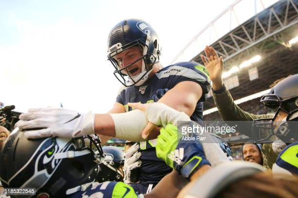 Jacob Hollister of the Seattle Seahawks celebrates with teammates after scoring the game-winning touchdown in overtime against the Tampa Bay...