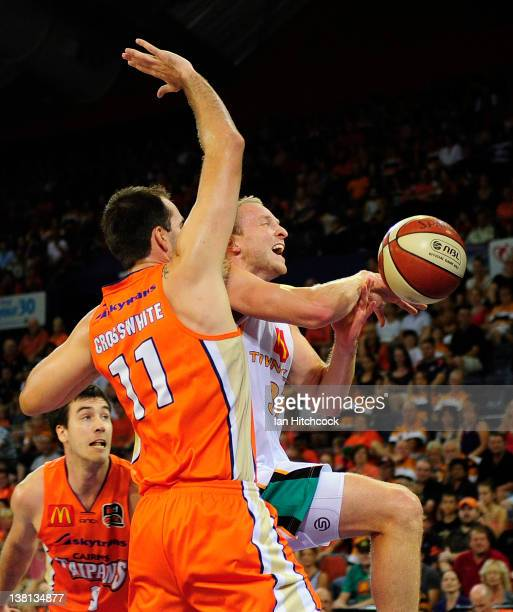 Jacob Holmes of the Crocodiles is blocked by Ian Crosswhite of the Taipans during the round 18 NBL match between the Cairns Taipans and the...