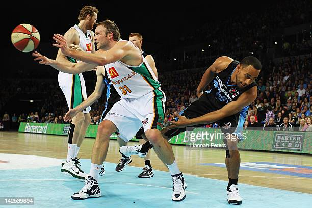 Jacob Holmes of the Crocodiles passes the ball out as Mika Vukona of the Breakers defends during game three of the NBL Finals series between the...