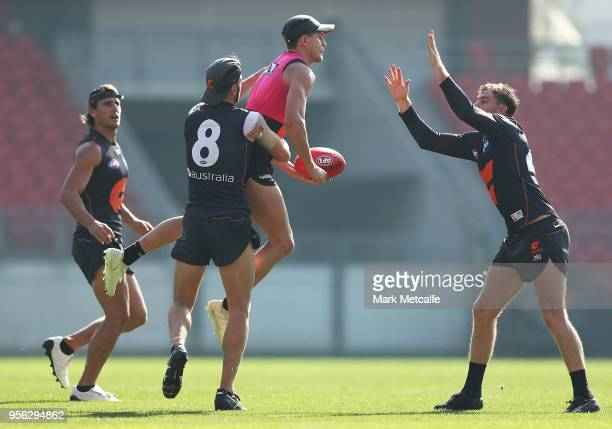 Jacob Hopper of the Giants is tackled by Callan Ward of the Giants during a Greater Western Sydney Giants AFL training session at Spotless Stadium on...