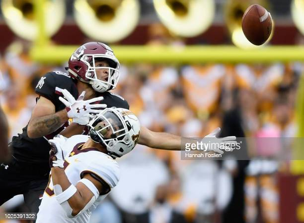 Jacob Huff of the Minnesota Golden Gophers collides with Johnathan Boone of the New Mexico State Aggies as they go for the pass during the first...