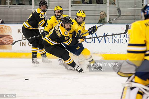 Jacob Johnstone of the Michigan Tech Huskies battles against Mac Bennett of the Michigan Wolverines on November 2 2013 at Yost Ice Arena in Ann Arbor...