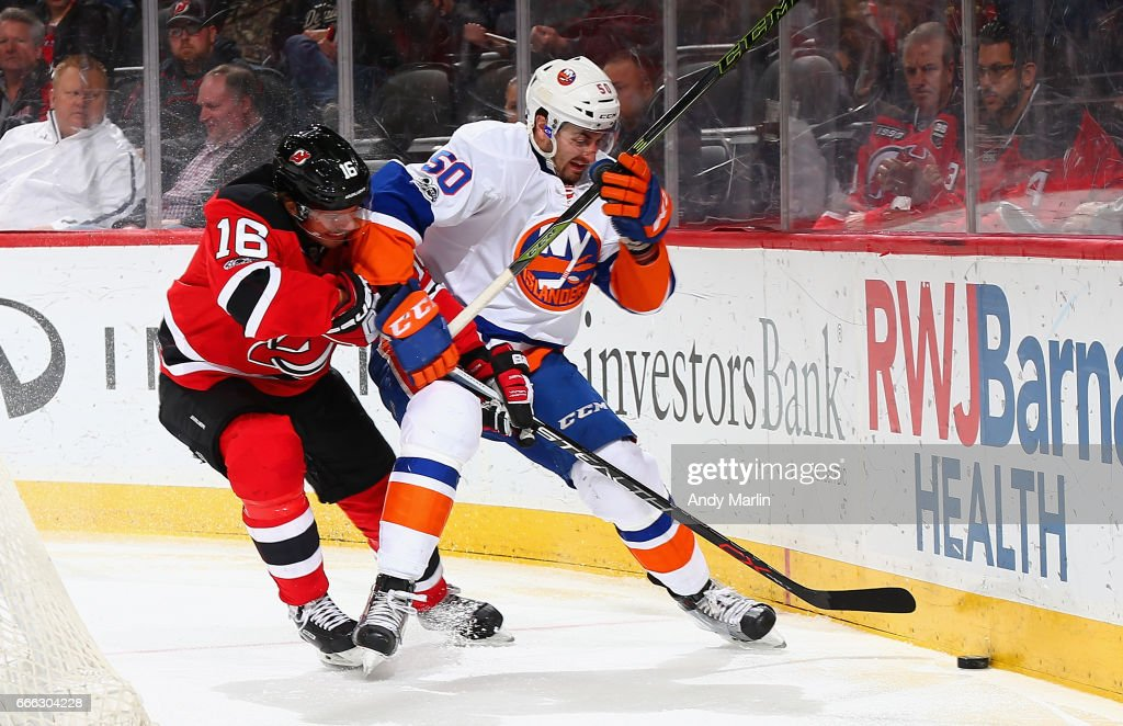 Jacob Josefson #16 of the New Jersey Devils and Adam Pelech #50 of the New York Islanders battle for control of the puck during the game at Prudential Center on April 8, 2017 in Newark, New Jersey.