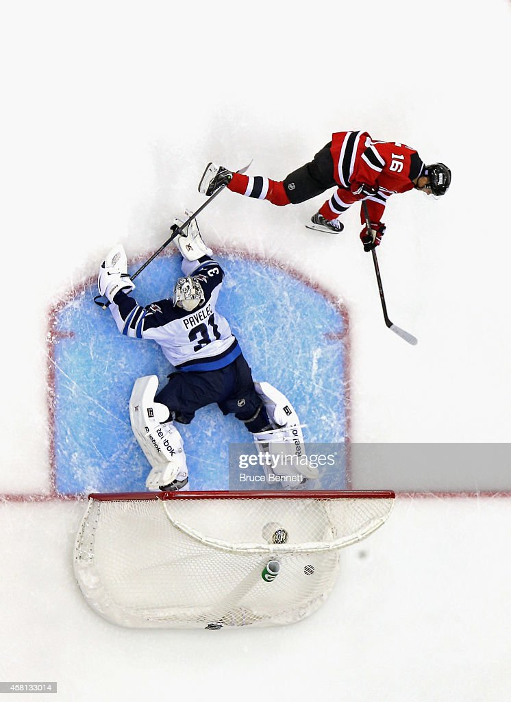 Jacob Josefson #16 of the New Jersey Devils scores the game winning goal during the shootout against Ondrej Pavelec #31 of the Winnipeg Jets at the Prudential Center on October 30, 2014 in Newark, New Jersey. The Devils defeated the Jets 2-1 in the shootout.