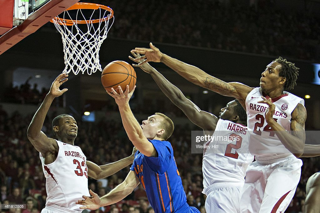 Jacob Kurtz #30 of the Florida Gators goes up for a layup past Michael Qualls #24 and Alandise Harris #2 of the Arkansas Razorbacks at Bud Walton Arena on January 11, 2014 in Fayetteville, Arkansas.