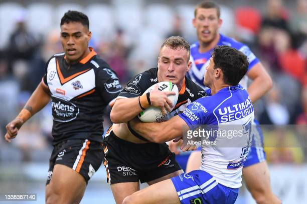 Jacob Liddle of the Tigers is tackled during the round 25 NRL match between the Wests Tigers and the Canterbury Bulldogs at Moreton Daily Stadium, on...
