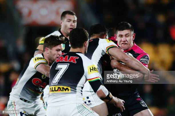 Jacob Lillyman of the Warriors charges into Josh Mansour of the Panthers during the round 19 NRL match between the New Zealand Warriors and the...