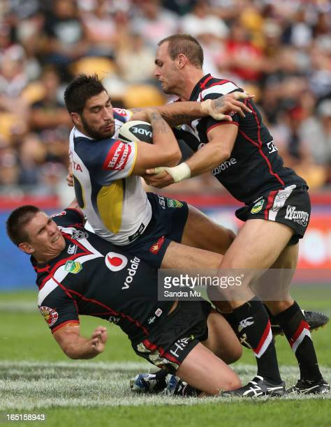 Jacob Lillyman of the Warriors is caught in the tackle of James Tamou of the Cowboys by Simon Mannering of the Warriors during the round four NRL...