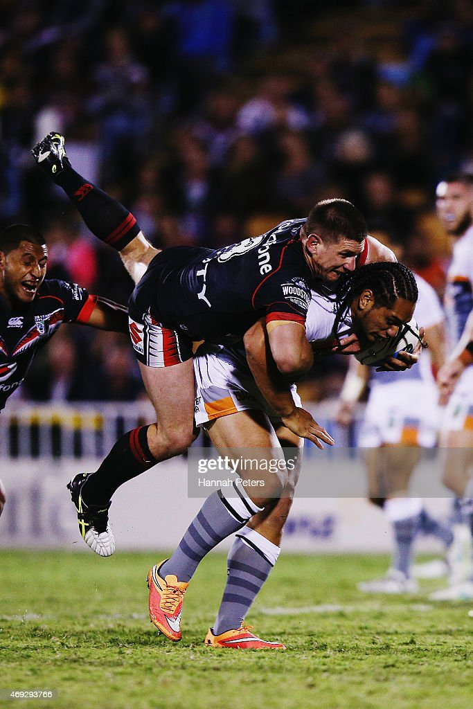 Jacob Lillyman of the Warriors tackles Martin Taupau of the Tigers during the round six NRL match between the New Zealand Warriors and the Wests Tigers at Mt Smart Stadium on April 11, 2015 in Auckland, New Zealand.