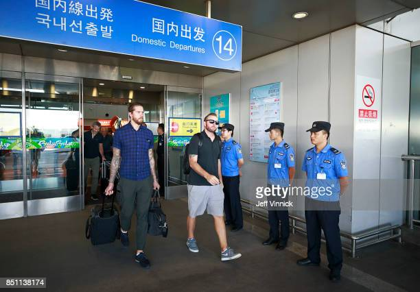 Jacob Markstrom and Thomas Vanek of the Vancouver Canucks walk past police officers after arriving at the Beijing airport September 22 2017 in...