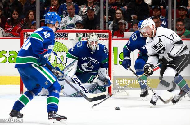 Jacob Markstrom Elias Pettersson and Alexander Edler of the Vancouver Canucks and Jeff Carter of the Los Angeles Kings watch a rebound during their...