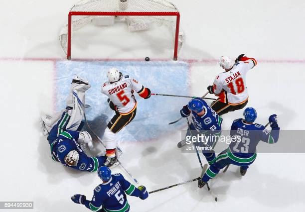 Jacob Markstrom of the Vancouver Canucks lays in his crease as Mark Giordano of the Calgary Flames scores his second goal during their NHL game at...