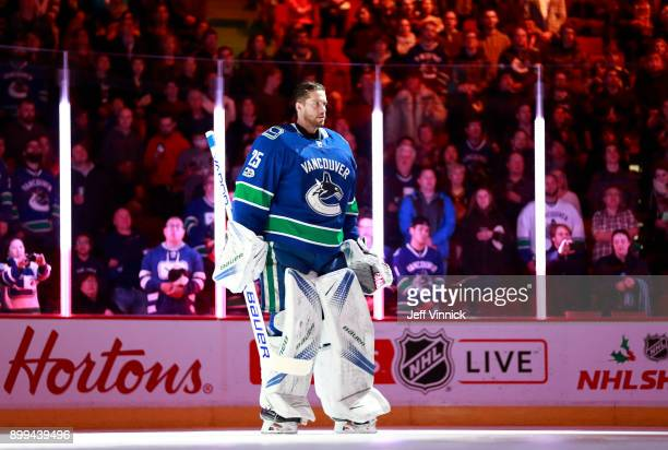 Jacob Markstrom of the Vancouver Canucks listens to the national anthem during their NHL game against the Carolina Hurricanes at Rogers Arena...