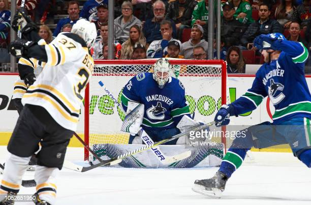 Jacob Markstrom of the Vancouver Canucks looks on as Alexander Edler of the Vancouver Canucks deflects the shot of Patrice Bergeron of the Boston...