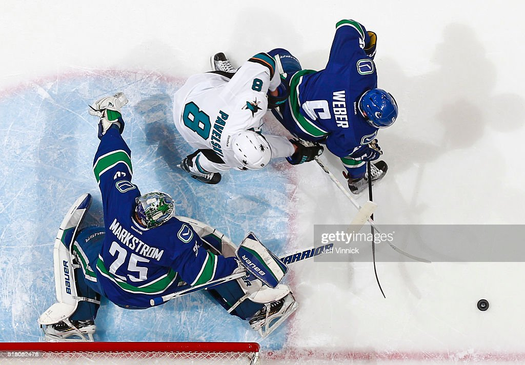 Jacob Markstrom #25 of the Vancouver Canucks makes a save while Joe Pavelski #8 of the San Jose Sharks and Yannick Weber #6 of the Canucks pursue the rebound during their NHL game at Rogers Arena March 29, 2016 in Vancouver, British Columbia, Canada. San Jose won 4-1.