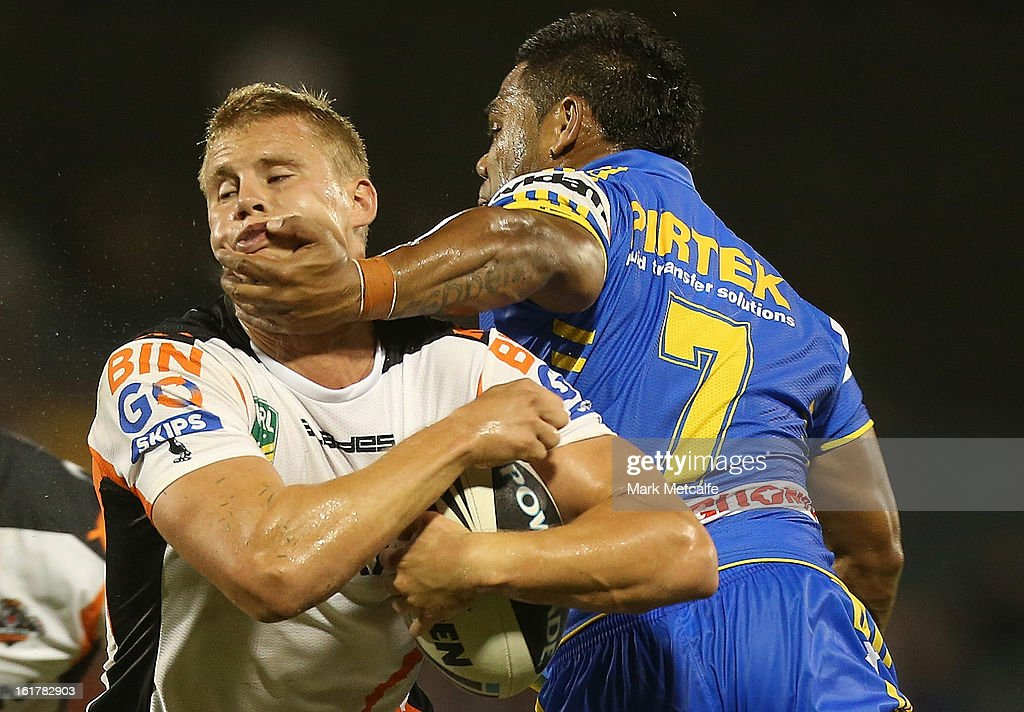 Jacob Miller of the Tigers is tackled by Chris Sandow of the Eels during the NRL trial match between the Wests Tigers and the Parramatta Eels at Campbelltown Sports Stadium on February 16, 2013 in Sydney, Australia.