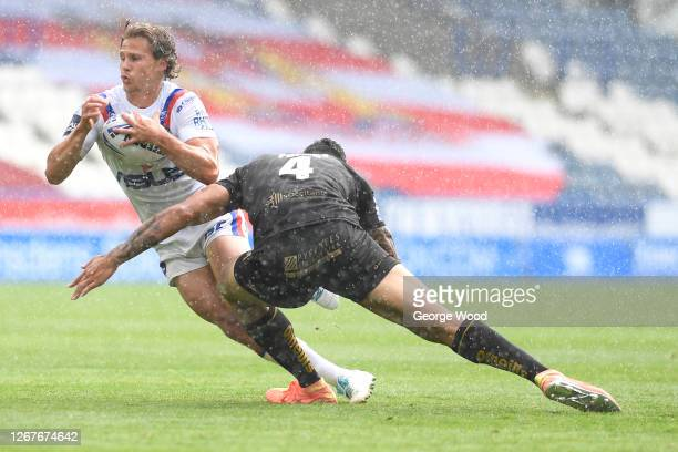 Jacob Miller of Wakefield Trinity is tackled by Israel Folau of Catalans Dragons during the Challenge Cup Round Six match between Catalans Dragons...