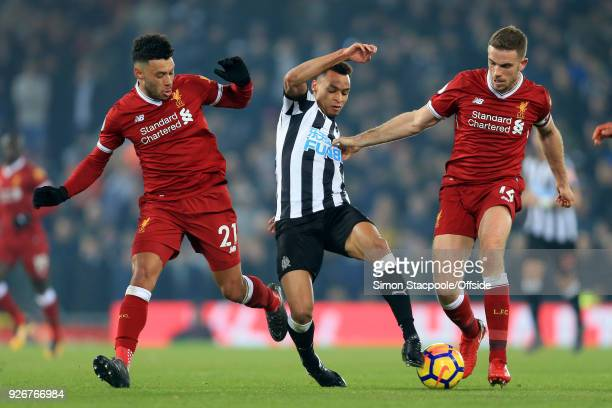 Jacob Murphy of Newcastle battles with Alex OxladeChamberlain of Liverpool and Jordan Henderson of Liverpool during the Premier League match between...