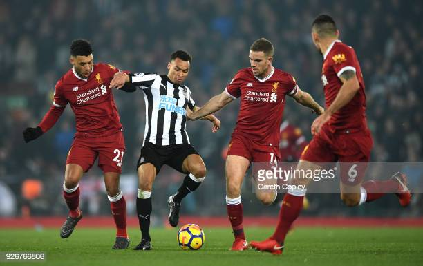 Jacob Murphy of Newcastle United is chased by Jordan Henderson and Alex OxladeChamberlain of Liverpool during the Premier League match between...