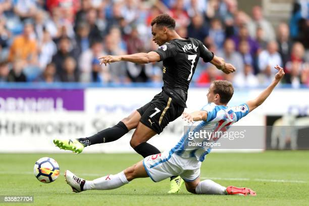 Jacob Murphy of Newcastle United shoots as Chris Lowe of Huddersfield Town attempts to block during the Premier League match between Huddersfield...