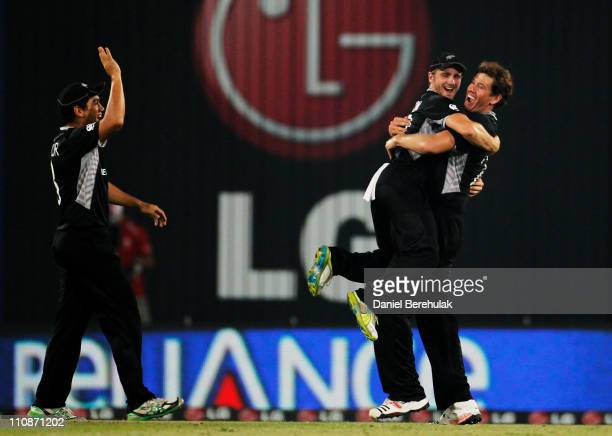 Jacob Oram of New Zealand celebrates with team mates Kane Williamson and Ross Taylor after taking the wicket of Robin Peterson of South Africa during...