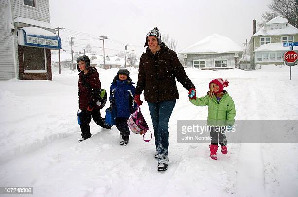 Jacob Raab, Alexander Raab, Alisa Raab and Ryan Raab navigate snow-covered streets after a five mile wide band of lake-effect snow dumped more than...