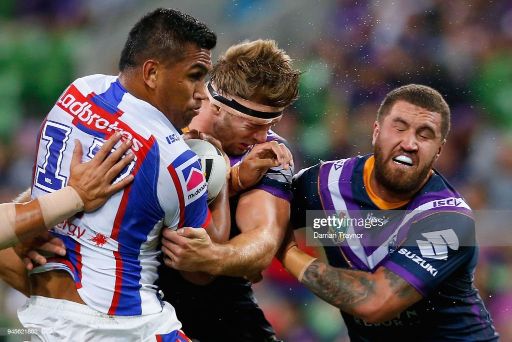 Jacob Saifiti of the Knights is tackled by Christian Welch of the Storm during the round six NRL match between the Melbourne Storm and the Newcastle Knights at AAMI Park on April 13, 2018 in Melbourne, Australia.
