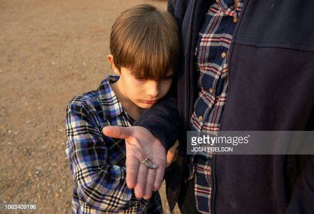 Jacob Saylors looks at the wedding ring his mother Zeatra Saylor found in the burned remains of their home in Paradise California on November 18 2018...