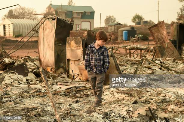 Jacob Saylors walks through the burned remains of his home in Paradise, California on November 18, 2018. - The family lost a home in the same spot to...