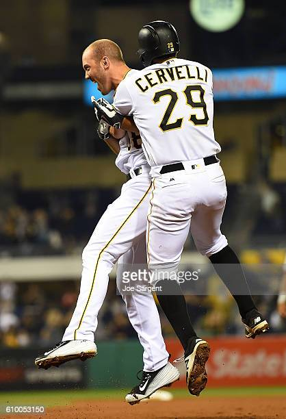 Jacob Stallings of the Pittsburgh Pirates celebrates his game winning RBI single with Francisco Cervelli during the eleventh inning against the...