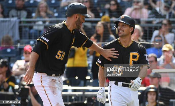 Jacob Stallings of the Pittsburgh Pirates celebrates with Adam Frazier after coming around to score on an RBI double by Starling Marte in the sixth...