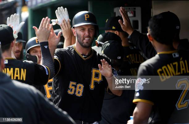 Jacob Stallings of the Pittsburgh Pirates celebrates with teammates in the dugout after coming around to score on an RBI double by Starling Marte in...