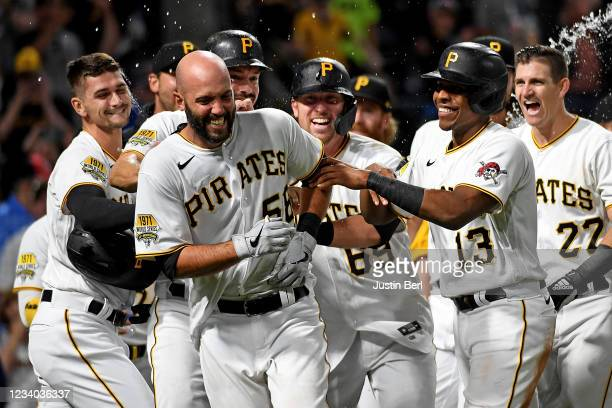 Jacob Stallings of the Pittsburgh Pirates is mobbed by teammates after Stallings hit a walk-off grand slam home run to give the Pirates a 9-7 win...