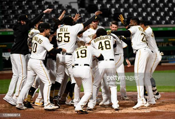 Jacob Stallings of the Pittsburgh Pirates is mobbed by teammates at home plate after hitting a walk off home run to give the Pirates a 3-2 win over...