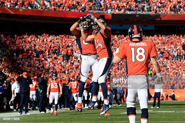 Jacob Tamme celebrates his second quarter touchdown with Eric Decker as Peyton Manning of the Denver Broncos looks on during their AFC Championship...
