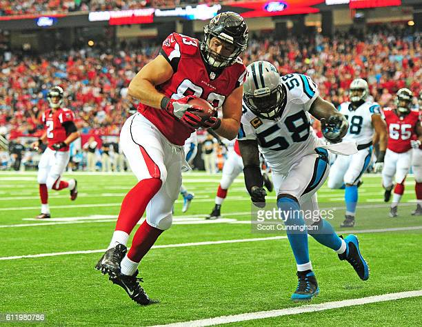 Jacob Tamme of the Atlanta Falcons runs with a catch for a first quarter touchdown against Thomas Davis of the Carolina Panthers at the Georgia Dome...