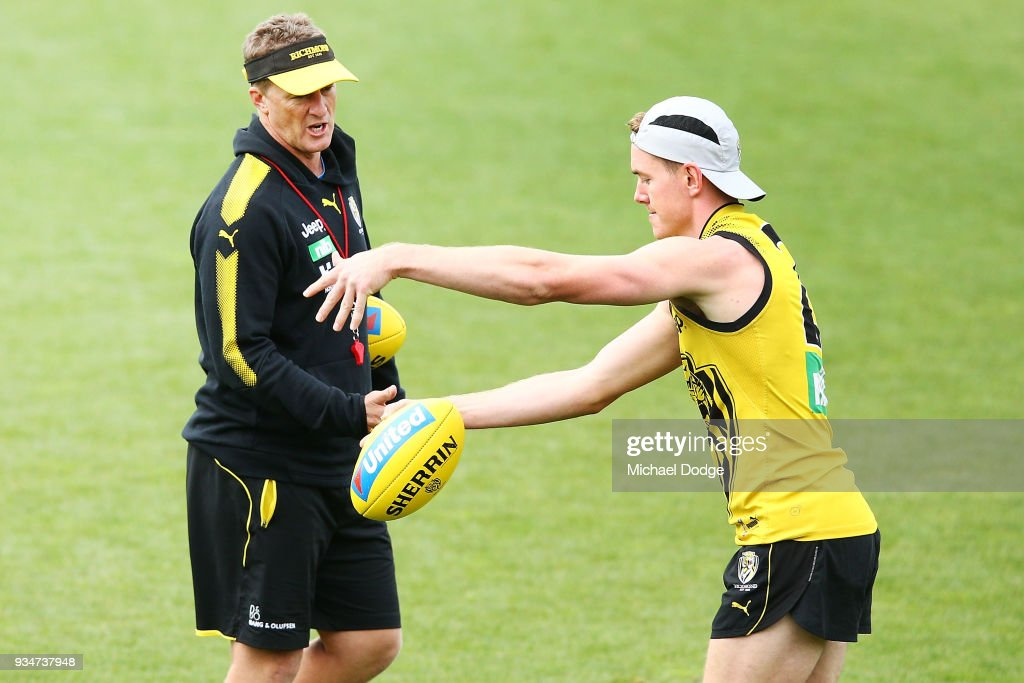 Jacob Townsend of the Tigers kicks the ball when listening to Tigers head coach Damien Hardwick during a Richmond Tigers AFL training session at Punt Road Oval on March 20, 2018 in Melbourne, Australia.