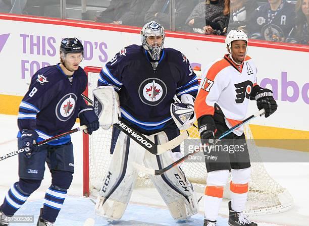 Jacob Trouba and goaltender Ondrej Pavelec of the Winnipeg Jets and Wayne Simmonds of the Philadelphia Flyers keep an eye on the play during...