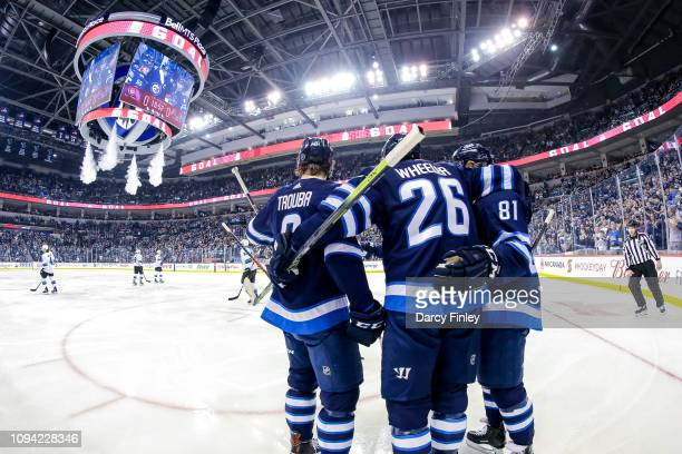 Jacob Trouba Blake Wheeler and Kyle Connor of the Winnipeg Jets celebrate a first period goal against the San Jose Sharks at the Bell MTS Place on...