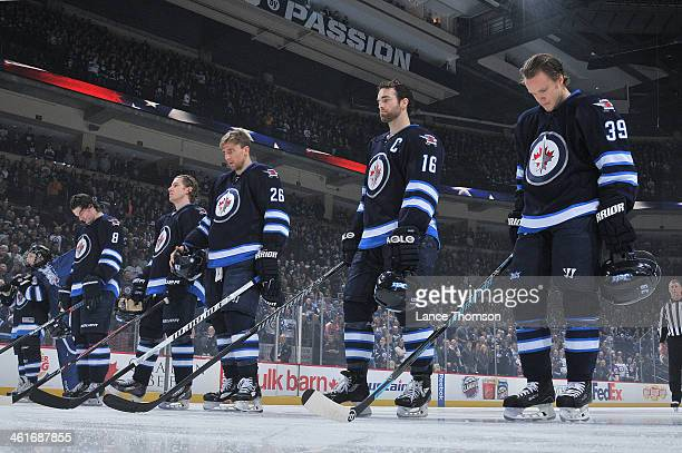 Jacob Trouba Bryan Little Blake Wheeler Andrew Ladd and Tobias Enstrom of the Winnipeg Jets stand on the ice during the singing of the National...