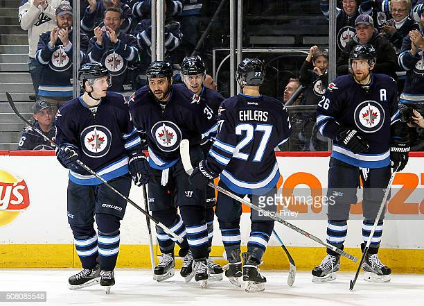 Jacob Trouba Dustin Byfuglien Mark Scheifele Nikolaj Ehlers and Blake Wheeler of the Winnipeg Jets skate to the bench after celebrating a third...
