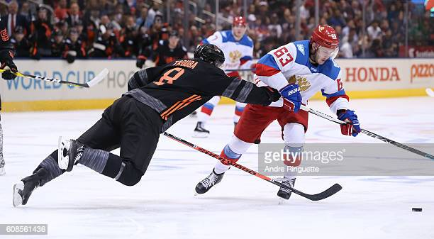 Jacob Trouba of Team North America dives to get the puck away from Evgenii Dadonov of Team Russia during the World Cup of Hockey 2016 at Air Canada...
