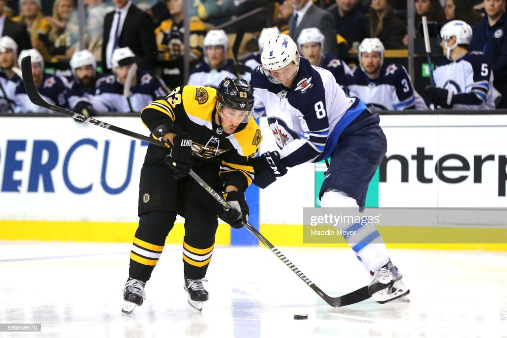 Jacob Trouba #8 of the Winnipeg Jets and Brad Marchand #63 of the Boston Bruins battle for control of the puck during the third period at TD Garden on December 21, 2017 in Boston, Massachusetts. The Bruins defeat the Jets 2-1 in a shoot out.