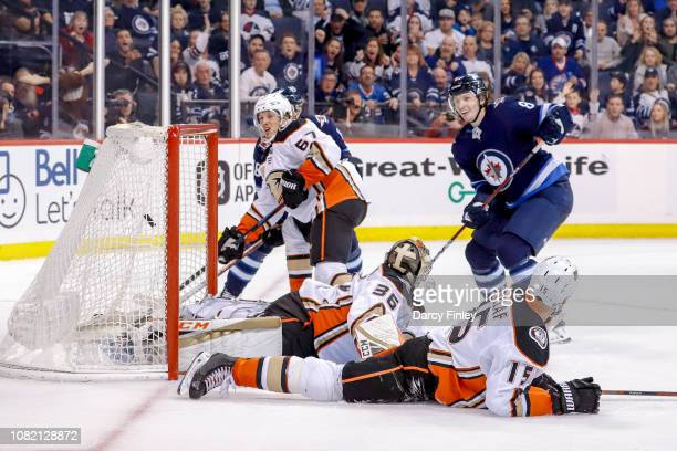 Jacob Trouba of the Winnipeg Jets and Rickard Rakell of the Anaheim Ducks watch as the puck flies into the net over a sprawled John Gibson for the...