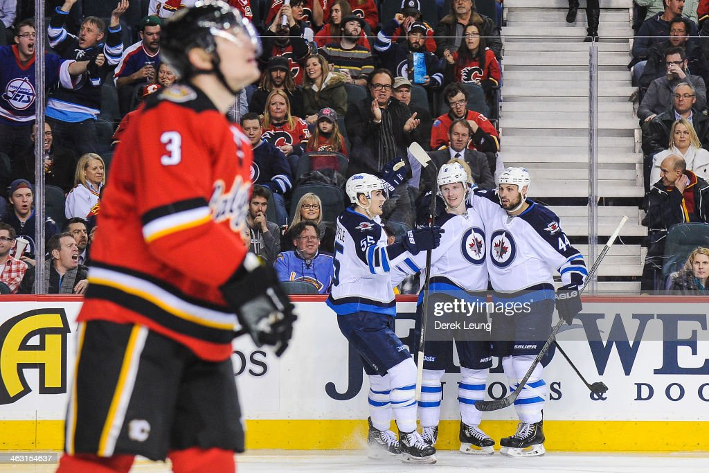 Jacob Trouba #8 (C) of the Winnipeg Jets celebrates his third period goal along with teammates Mark Scheifele #55 (L) and Zach Bogosian #44 (R) while Ladislav Smid #3 of the Calgary Flames skates away during an NHL game at Scotiabank Saddledome on January 16, 2014 in Calgary, Alberta, Canada. The Jets defeated the Flames 5-2.