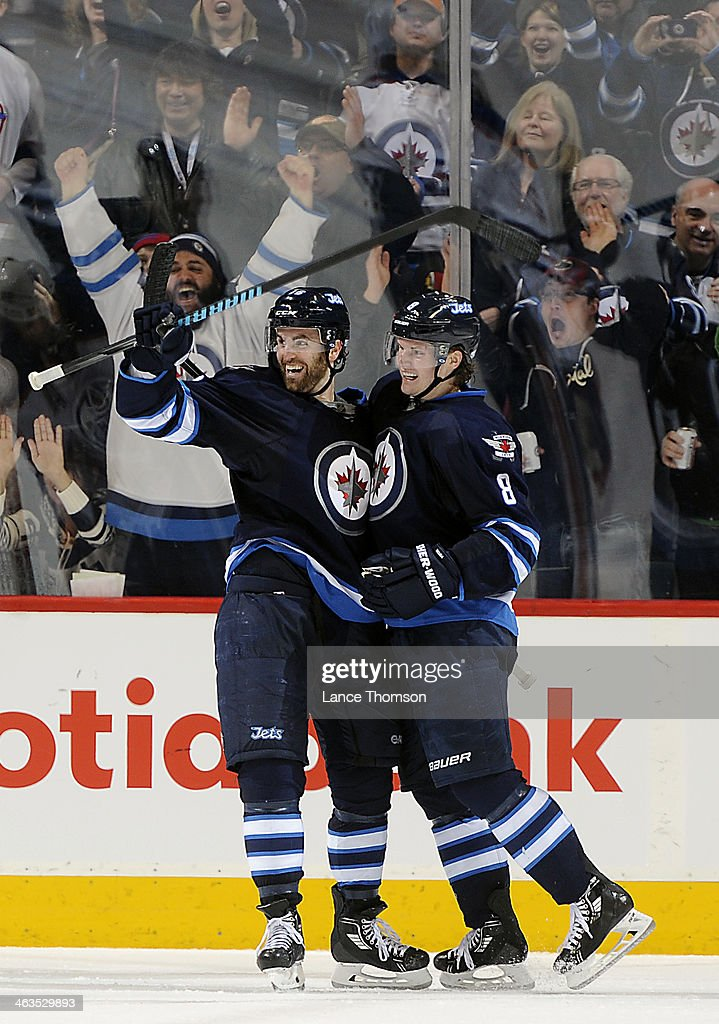 Jacob Trouba #8 of the Winnipeg Jets celebrates with teammate Andrew Ladd #16 after scoring a third period goal against the Edmonton Oilers at the MTS Centre on January 18, 2014 in Winnipeg, Manitoba, Canada.