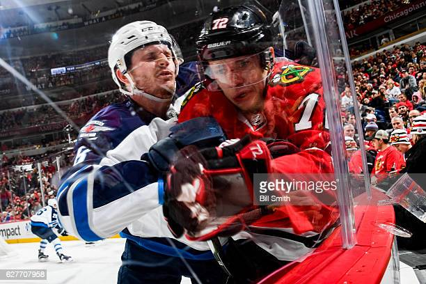 Jacob Trouba of the Winnipeg Jets checks Artemi Panarin of the Chicago Blackhawks into the boards in the first period at the United Center on...